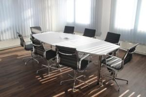 Neuvottelutilan tyhjä pöytä, jossa tuoleja ympärillä.