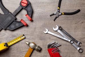 Erilaisia työkaluja; Vasara, puristin, rullamitta, kiintoavaimia ja pihdit